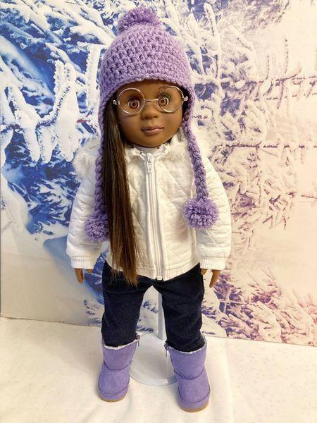 Black Dollz Rock online craft business. doll wearing crochet purple hat, purple boots, glasses, long hair braid, black pants, and white coat.